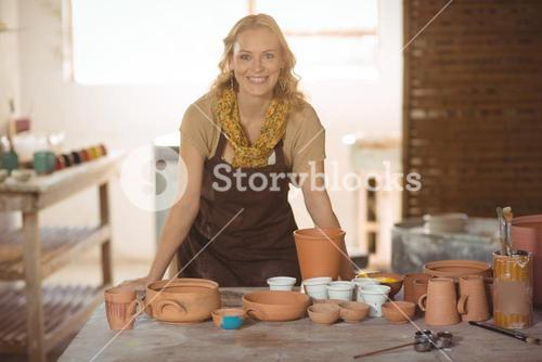 Beautiful female potter leaning on worktop