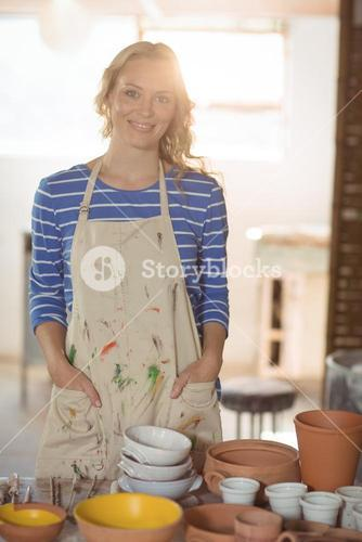 Beautiful female potter standing in pottery shop