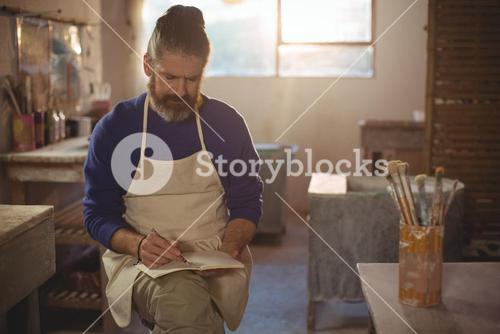 Male potter writing in notebook