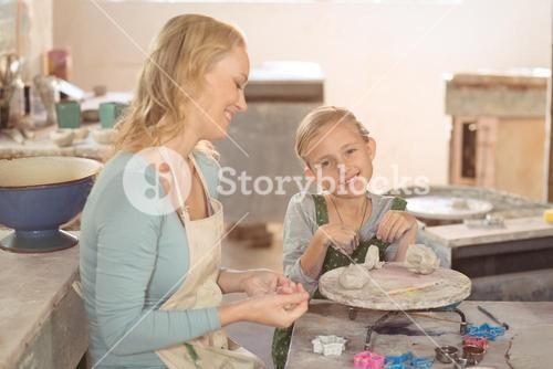 Female potter and girl working in workshop