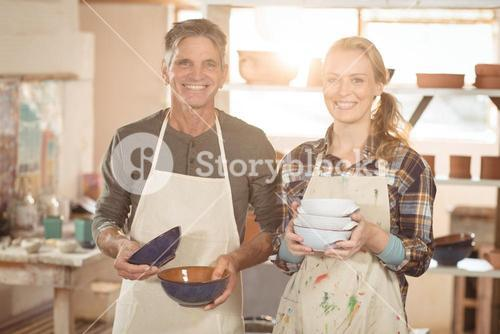 Potters holding pottery in workshop