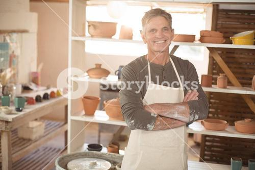 Smiling male potter standing with arms crossed in pottery workshop