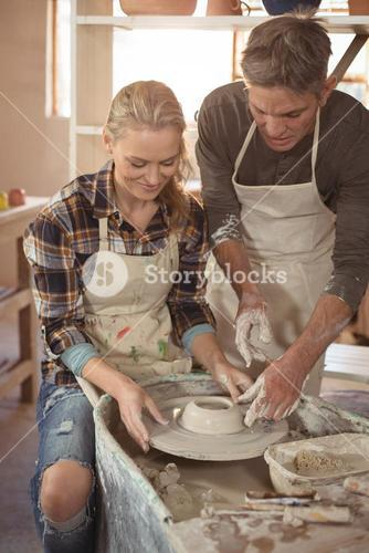 Male potter assisting female potter