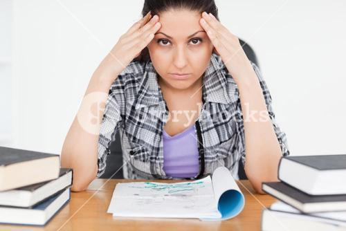 Stressed student with homework looking to camera