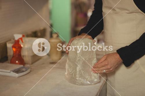 Male potter removing plastic cover from molding clay