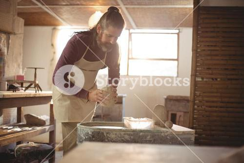 Male potter putting clay pottery wheel in pottery workshop