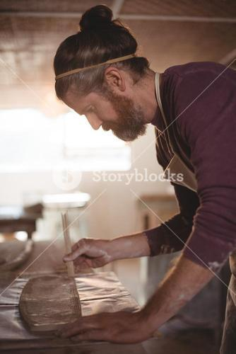 Male potter designing clay with sticks