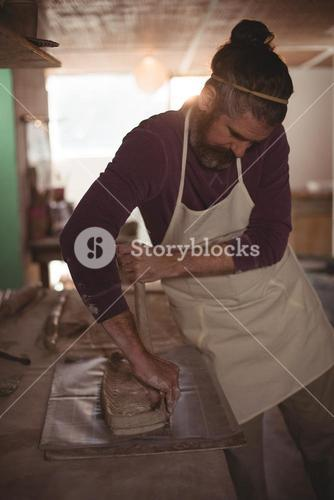 Male potter designing clay with stick