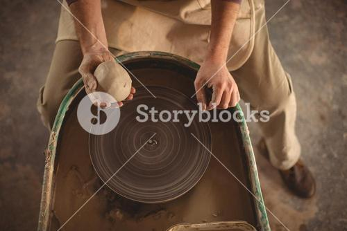 Male potter holding clay