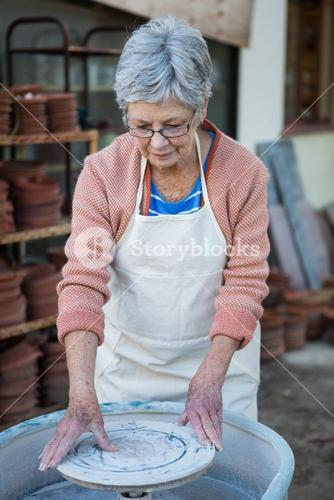 Female potter checking pottery wheel