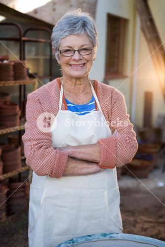 Happy female potter standing in pottery workshop