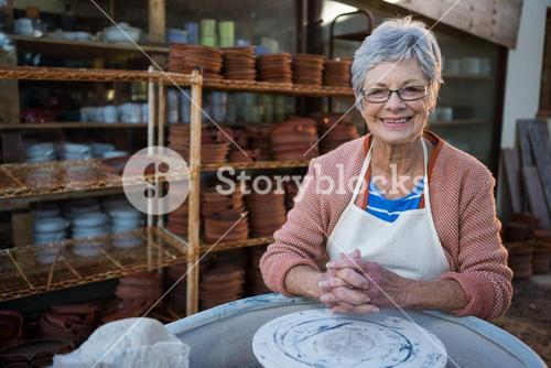Female potter smiling in pottery workshop