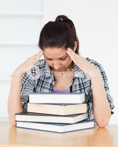 Frustrated young student leaning on books