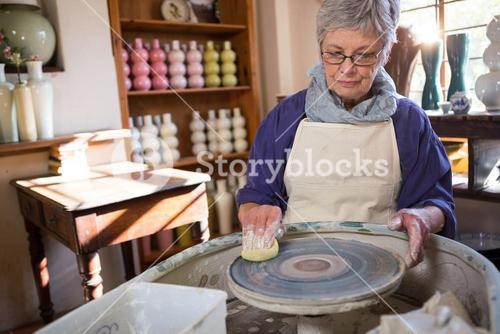Female potter cleaning pottery wheel