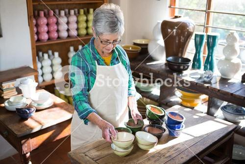 Female potter arranging bowl on worktop