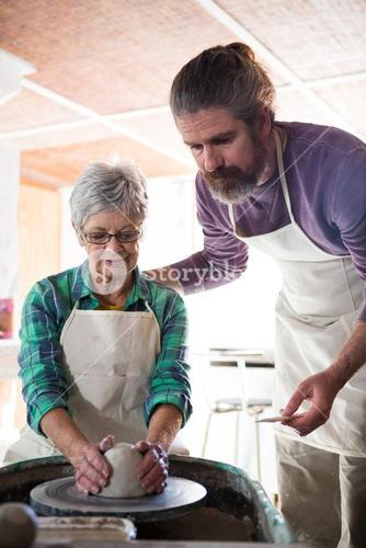 Male potter assisting female potter while making pot