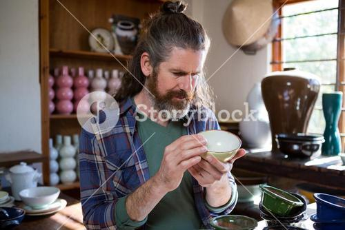 Male potter checking bowl
