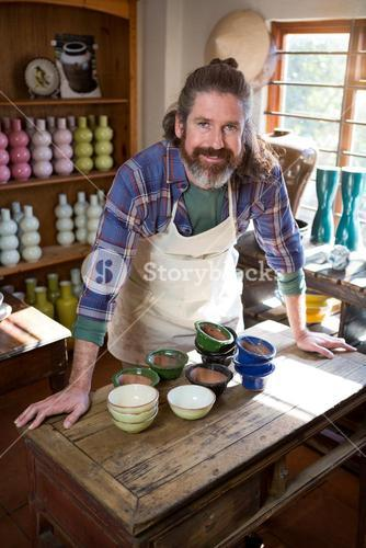 Portrait of male potter standing at table