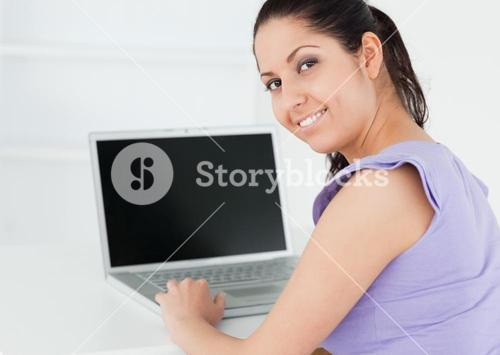 Cute young woman sitting by laptop