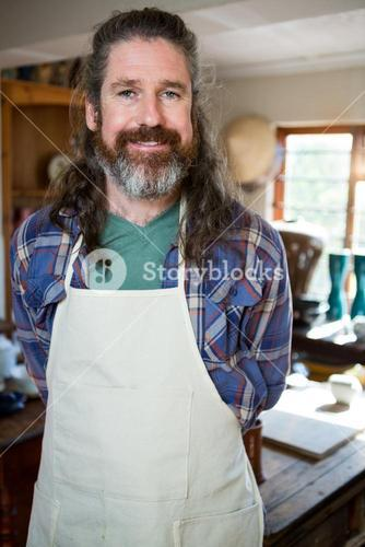 Portrait of male potter standing in pottery workshop
