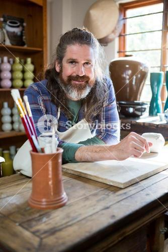 Portrait of male potter in pottery workshop