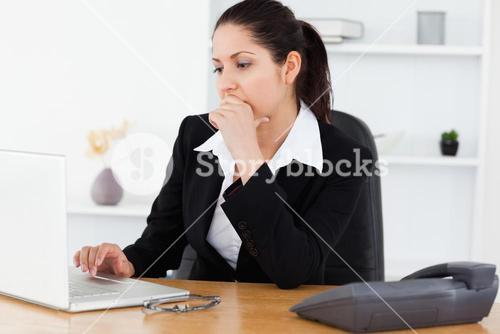 Serious young businesswoman in office