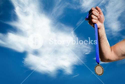 hand holding medal over sky background
