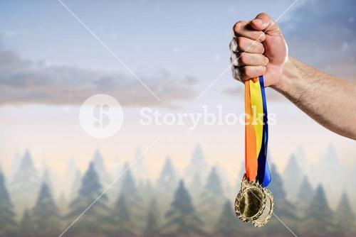 hand holding medals over nature background
