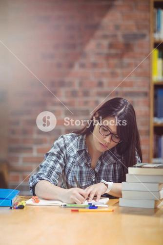 Female student writing notes in library