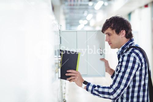 Student keeping his book in the locker