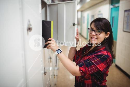 Female student keeping her book in the locker