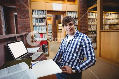 Smiling student sitting in library