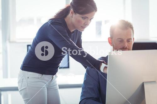 Teacher assisting mature student in computer room