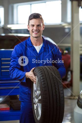 Portrait of mechanic holding a tyre