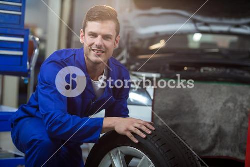 Portrait of mechanic with a tyre