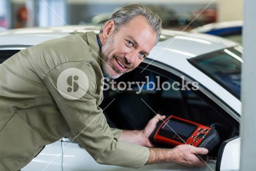 Portrait of mechanic using a diagnostic tool