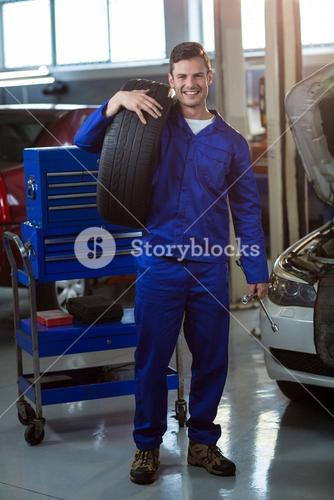 Portrait of mechanic carrying a tyre