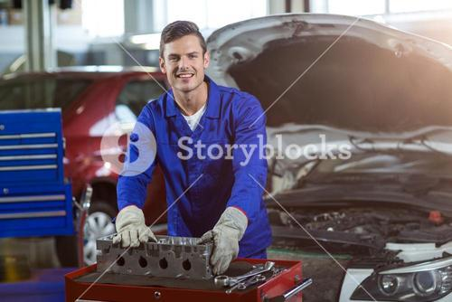 Portrait of mechanic checking a car parts