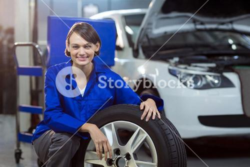 Portrait of female mechanic with a tyre