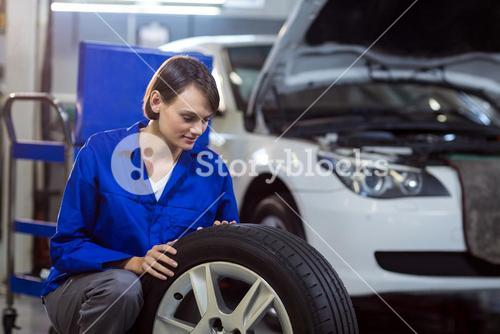 Female mechanic checking a tyre