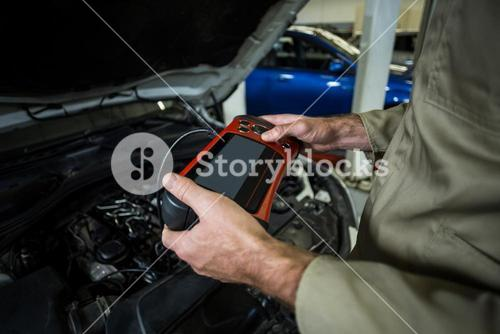 Hands of mechanic using a diagnostic tool