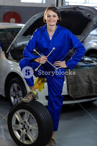 Portrait of female mechanic standing with a tyre