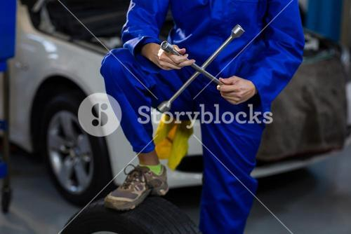 Mid-section of female mechanic with lug wrench