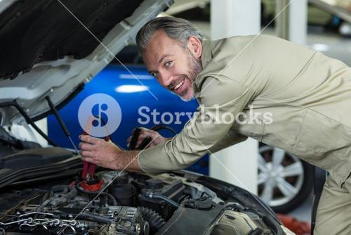 Mechanic attaching jumper cables to car battery