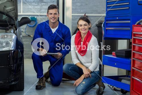 Mechanic holding digital tablet with customer