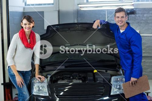 Mechanic and customer standing with car