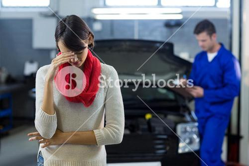 Worried customer standing while mechanic examining car in background