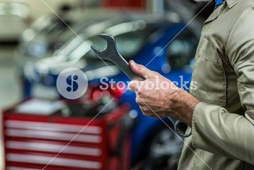 Mid-section of mechanic holding wrench tool