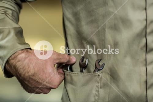 Mid-section of mechanic with wrench tool in his pocket