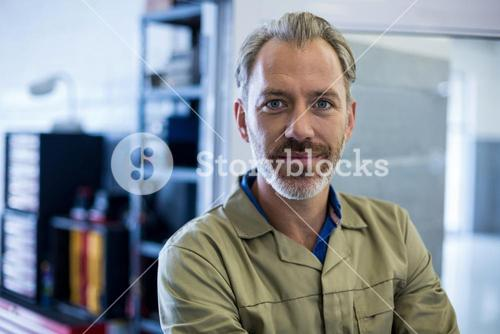 Smiling mechanic standing in repair shop
